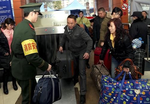 上海/2月5日,在上海长途汽车客运南站,检查人员准备对一名进站旅客...